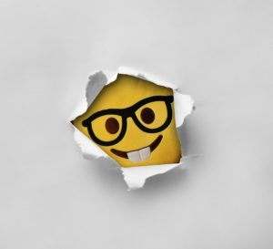 Smiley mit Brille bricht durch Wand